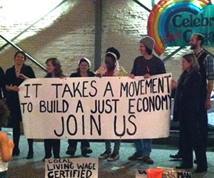 group of volunteers holding economic justice sign
