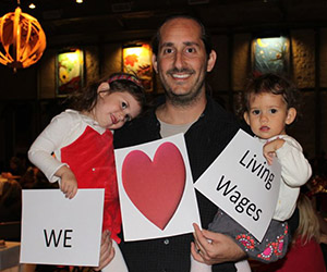 father and kids holding up we love living wages signs